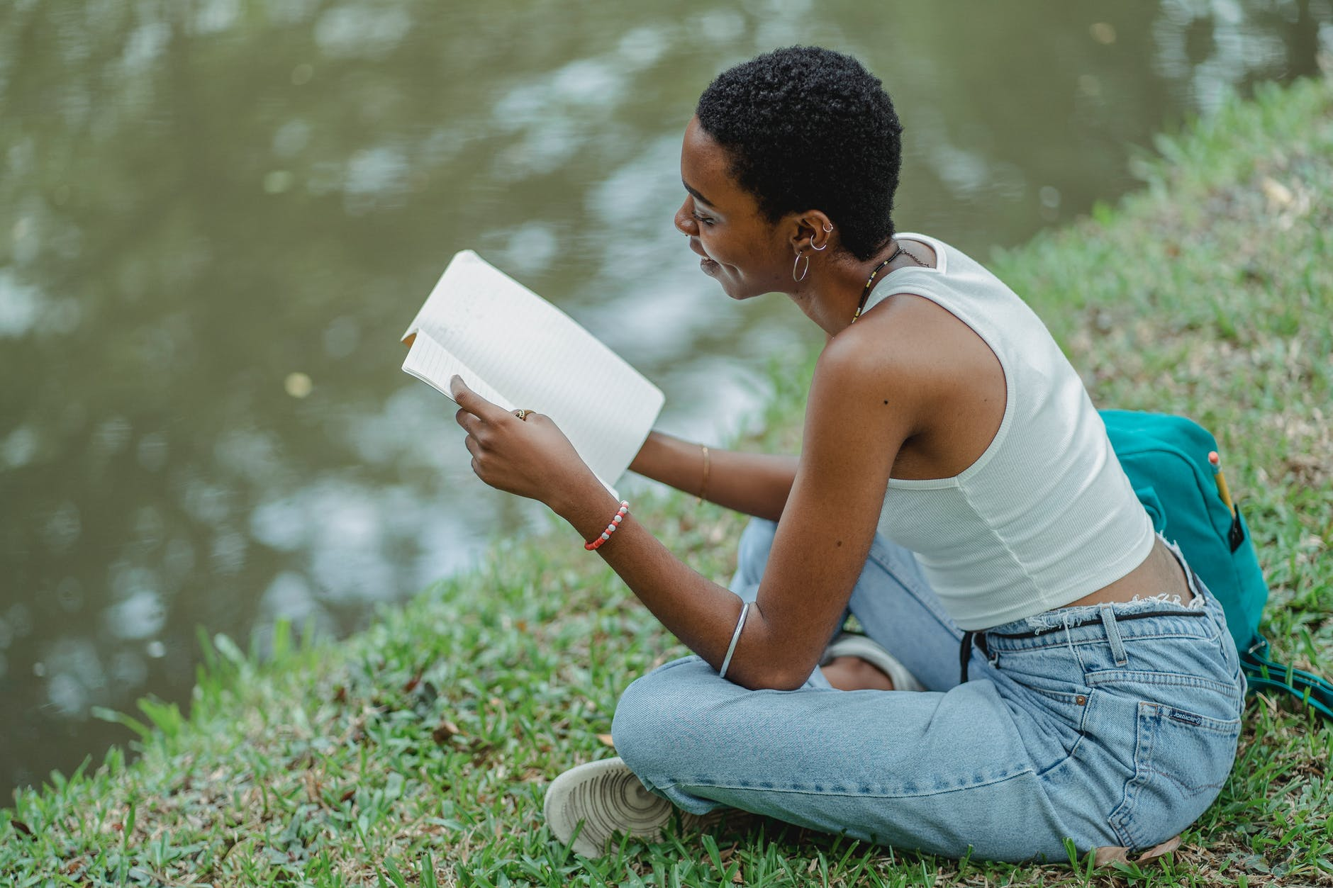 black young student reading textbook while resting near lake