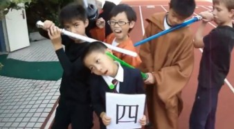 """A group of little boys in Halloween costumes holding up the Chinese character for """"4"""" in a Death to Giants music video."""