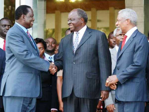 Former UN secretary general Kofi Anan watches as Opposition leader Raila Odinga and President Mwai Kibaki shake hands outside Harambee House, after brokering a peace deal in 2008 following post-election violence. /FILE