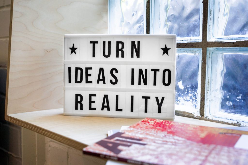 """The image shows a sign that says """"Turn Ideas Into Reality"""""""