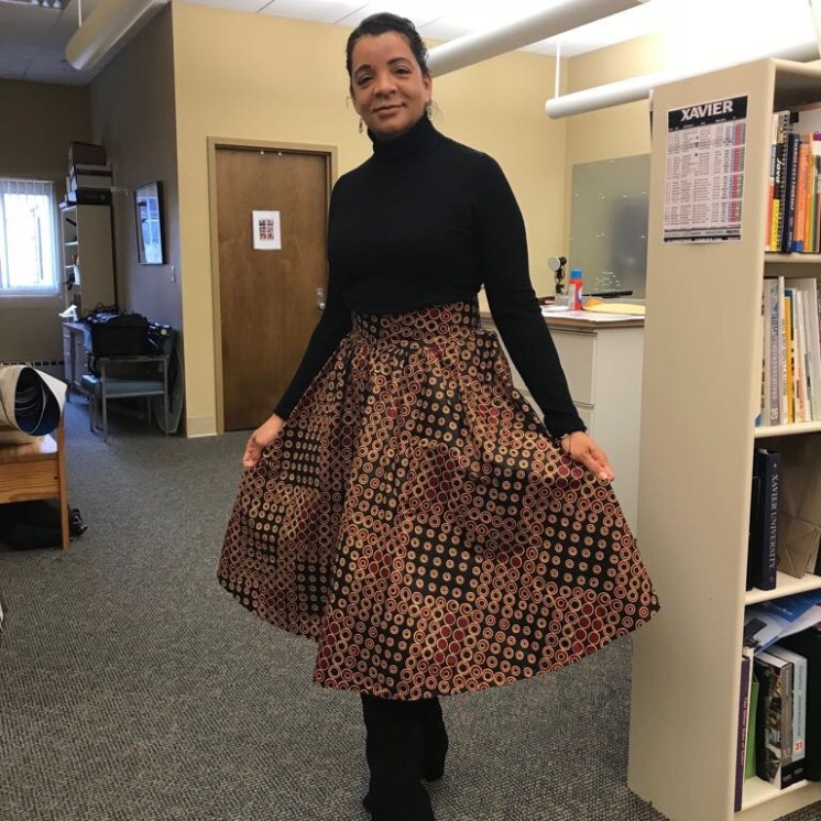 Audrey is wearing the skirt portion of her hand-tailored outfit back to campus with black knee-high boots and turtle neck.