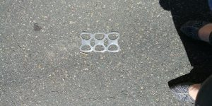 a plastic connective ring for a six pack of canned beverages living in the street