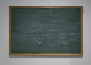 Repurposed school chalkboard where people have written the names of souls who will not be remembered by history