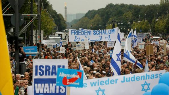 People listen to speakers during anti-Semitism demo at Berlin's Brandenburg Gate