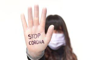 """Eine Frau mit Alltagsmaske steckt die rechte Hand mit dem Text """"Stop Corona"""" entgegen."""