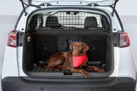 Sind Haustiere oder schwere Gegenstände mit an Bord, sorgt ein stabiles Laderaumtrenngitter dafür, dass diese im Falle einer Vollbremsung weiterhin sicher im Kofferraum bleiben. Foto: Opel