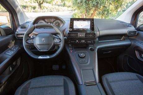 Typisch Peugeot: Das abgeflachte Lenkrad mit dem Cockpit darüber. In der Mittelkonsole: großes Staufach, Automatik-Wählrad und Touchscreen. © Peugeot