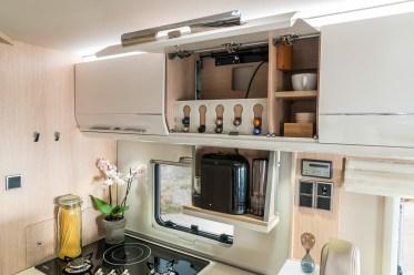 Die Küche verfügt neben dem manuell ganz leicht absenkbaren Kaffeemaschinenauszug zusätzlich über einen eigens angefertigten Kapselhalter - für verschiedenste Kaffeespezialitäten im Handumdrehen. Foto: Hymer