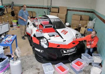 Axel A-Rubaie (links) und Pascal Lenhard bauen einen halben Porsche 911 RSR aus Lego, die andere Hälfte stammt vom Originalfahrzeug. Foto: Auto-Medienportal.Net/Axel F. Busse