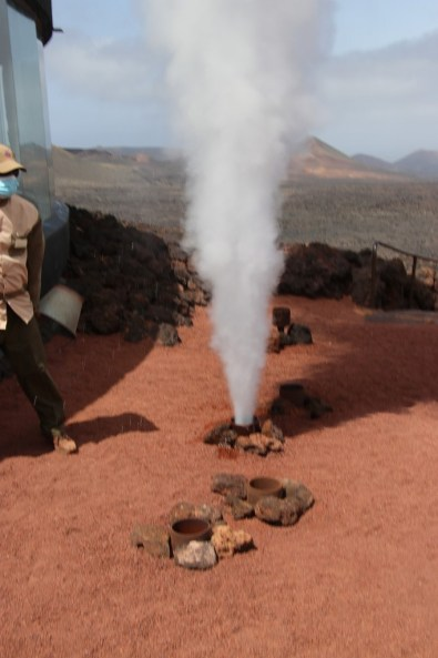Ein Ranger kippt Wasser in ein Erdrohr, so dass dieses nach wenigen Sekunden als Geysir in die Höhe schießt. © Kurt Sohnemann
