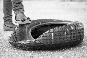 wrecked old tire on the street and girls foot on it d2666m