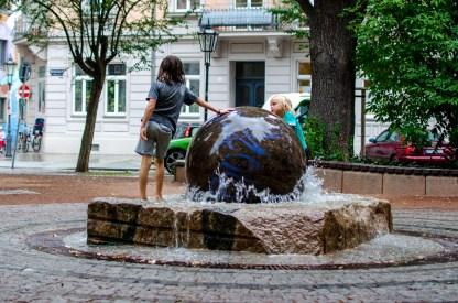 Foto von Luis und Bela, die am Brunnen am Martin-Luther-Platz in Dresden Neustadt spielen.