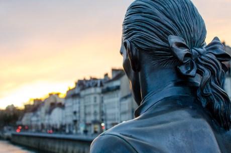 Ein Foto eines Hinterkopfes einer Skulptur, die am Fluss entlang über Besançon blickt.