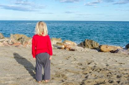 Foto eines Kindes am Strand von Le Barcarès, das die Aussicht auf das Meer genießt.
