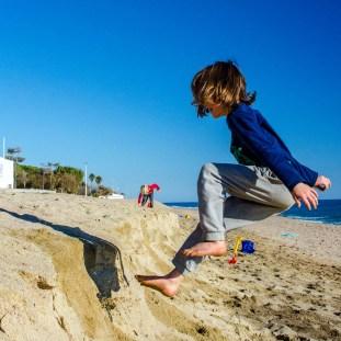 Foto eines Kindes beim Springen im Sand am Strand von Pineda de Mar.