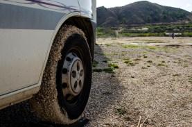 """Foto von einem Reifen eines Wohnmobils, mit Schlamm und Steinen """"paniert"""""""