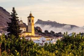Foto der Kirche in Ricote, mitten in den Bergen, in denen eine Wolke hängt.
