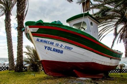 Foto von einem alten Holzboot an der Strandpromenade.