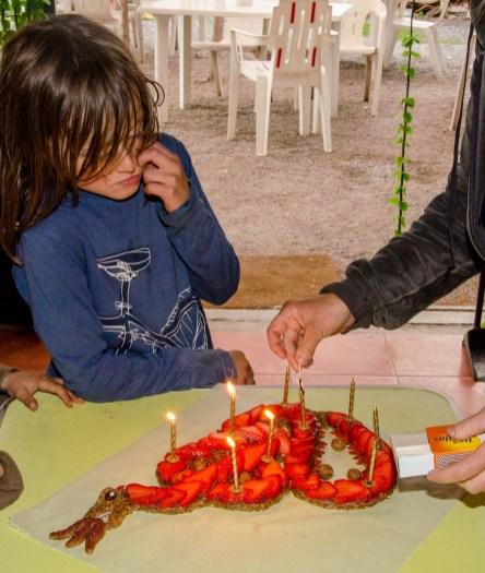 Foto von Kind mit Geburtstagskuchen, es werden gerade neun Kerzen angezündet.