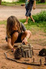 Kind baut mit Naturmaterialien.