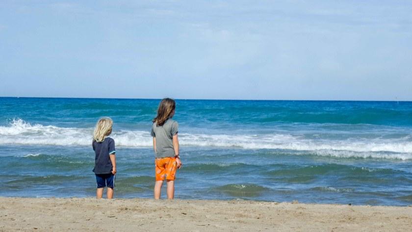 Zwei Kinder mit dem Blick auf das Meer.