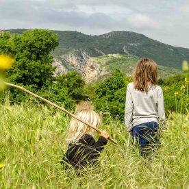 Kinder im hohen Gras, im Hintergrund Berge.