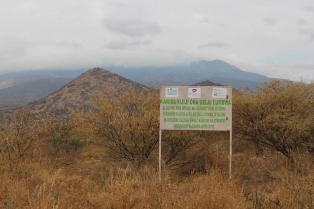 Een bord dat grasland afbakent voor de Masai-veehouders en hun kuddes