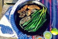 Seglerküche Paellapfanne auf Tisch mit grünem Spargel und Hähnchen BBQ
