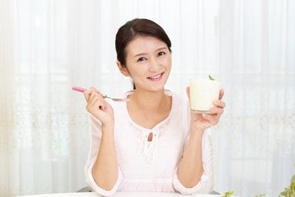 ヨーグルトを持つ笑顔の女性