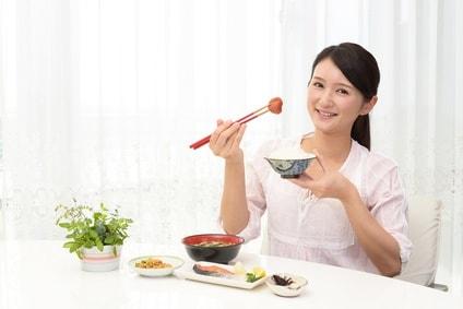 箸で梅干しを持つ女性