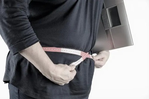 femme de 50 ans qui veut perdre du poids elle à un centimètre autour de la taille et une balance sous le bras