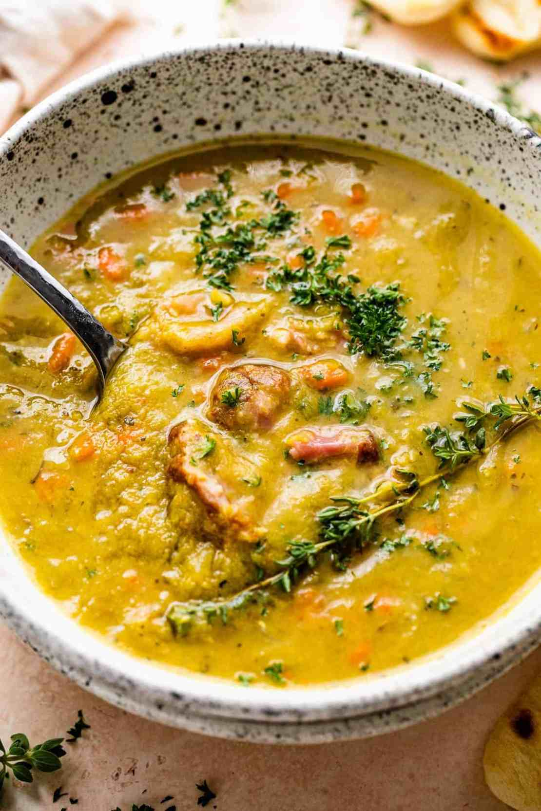 split pea soup in a bowl with chunks of ham and herbs on top