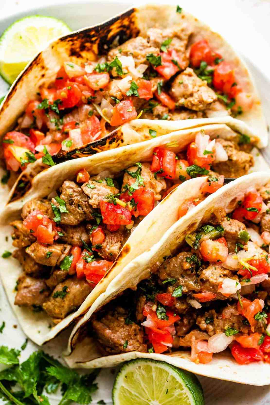 overhead close up shot of three pork carnitas tacos served on a round plate with pico de gallo