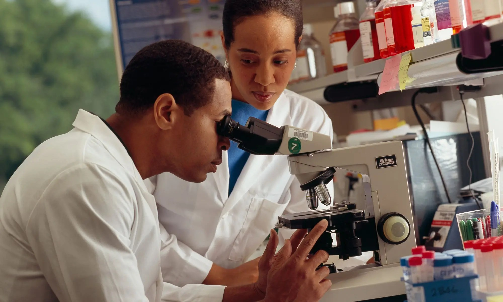 image of Researcher looking through microscope