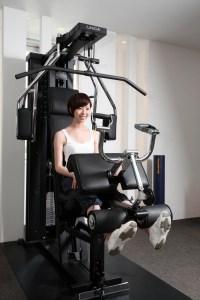 ウエイトマシンの重りをあげる女性