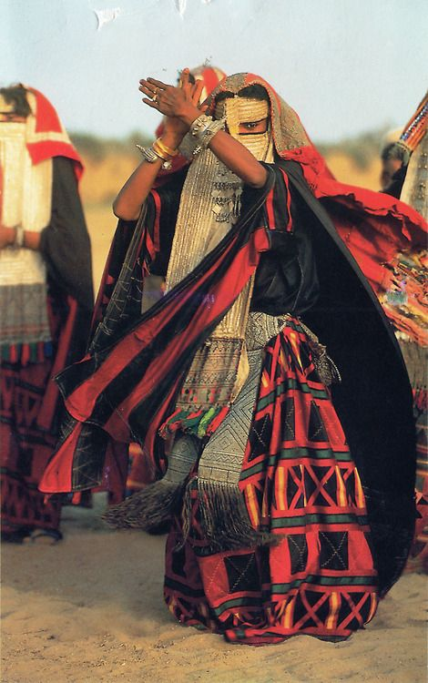 Arab woman wearing traditional red and black dress dancing