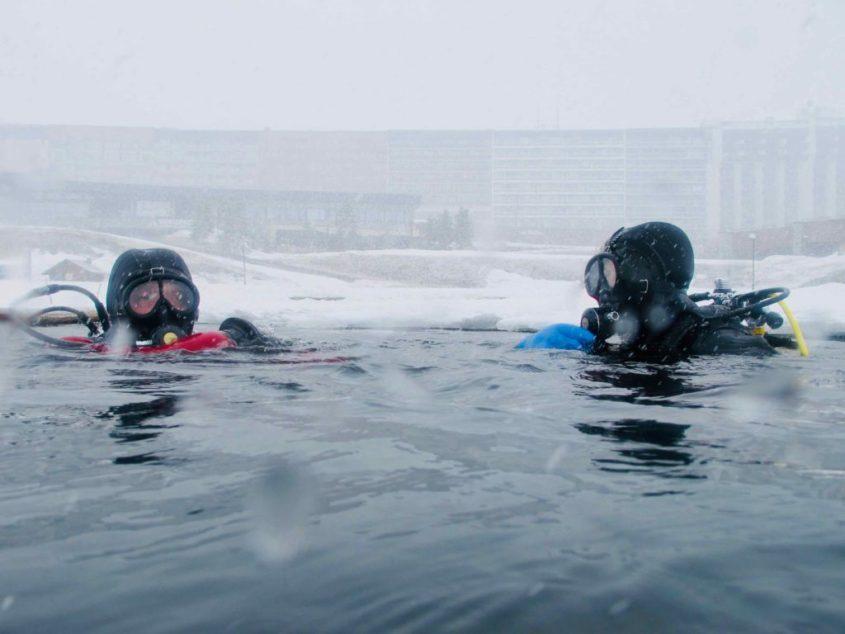 Deux plongeurs sous glace à Tignes entrent dans l'eau