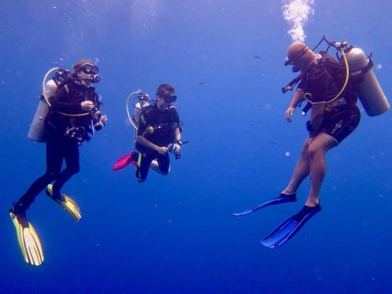 Deux plongeurs occupés à passer un premier niveau de plongée avec leur moniteur en Egypte.
