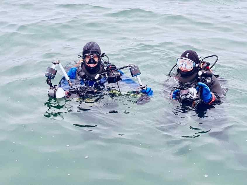 Deux plongeurs photographes s'apprêtent à plonger