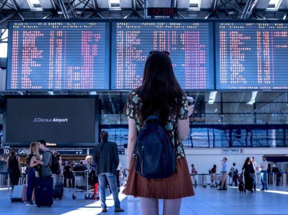 Une femme regarde les tableaux d'arrivées et de départs dans un aéroport