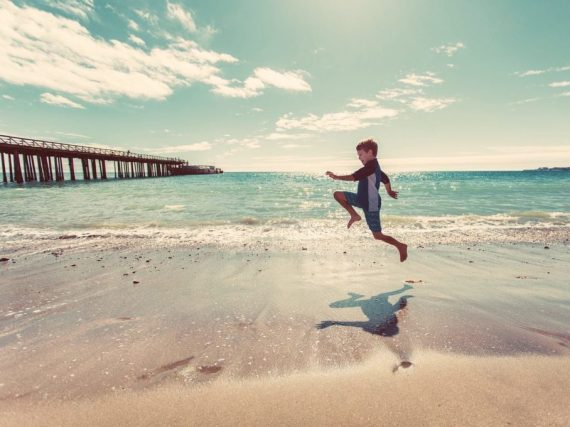 Un enfant joue devant l'océan
