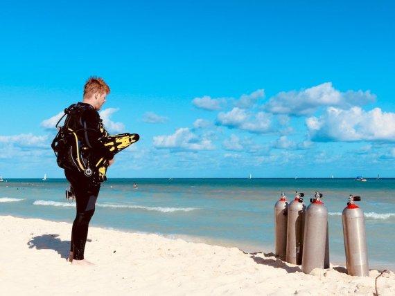 Un plongeur regarde les bouteilles de plongées au bord de la mer