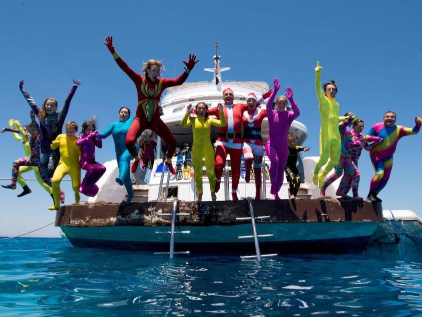 Des plongeurs en tenues multicolores sautent tous ensembles d'un bateau