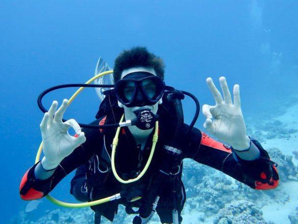 Check du matériel de plongée. Un plongeur fait le signe ok avec ses deux mains pour signifier qu'il l'a bien réalisé