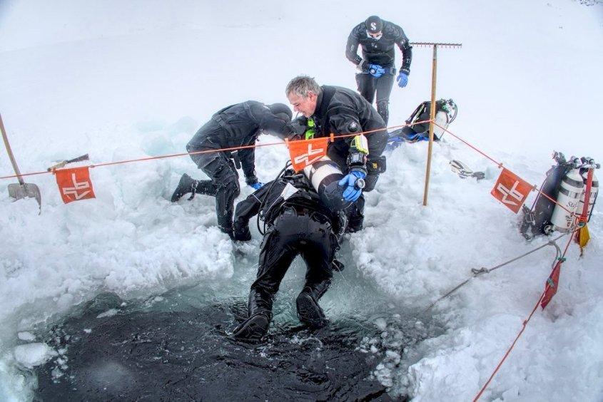 Des plongeurs aident un autre à sortir de l'eau gelée.