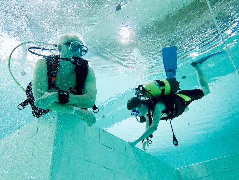 Un professeur de plongée est occupé a regarder devant lui dans la piscine pendant qu'un enfant plonge à côté de lui.