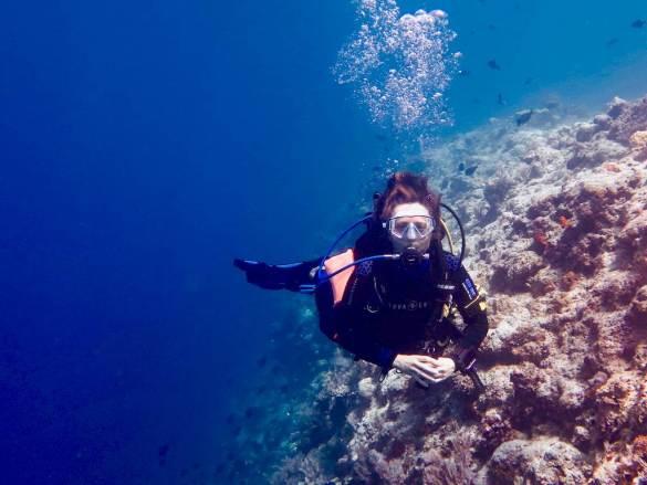 Une plongeuse longe un récif