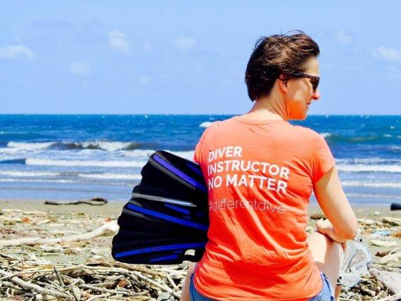"""Hélène assise sur la plage avec ses palmes et son masque. Elle arbore un t-shirt avec écrit dessus """"divers, instructeur, no matter #differentdive"""""""