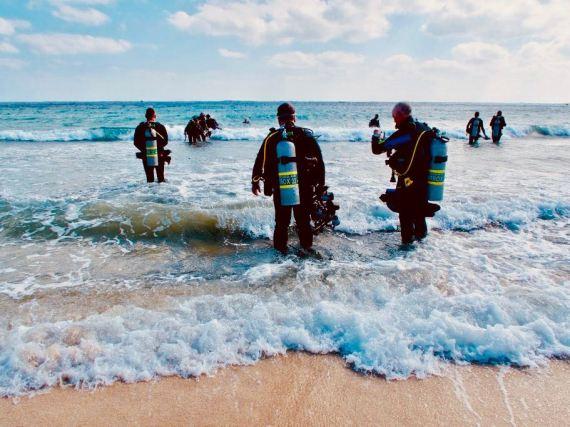 covid et plongée doivent être pris au sérieux lors de la reprise de la plongée comme pour ces plongeurs au bord de l'eau.
