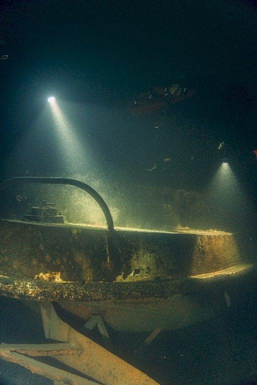 Des plongeurs éclairent le remorqueur de 10 mètres posé sur le fond de la carrière